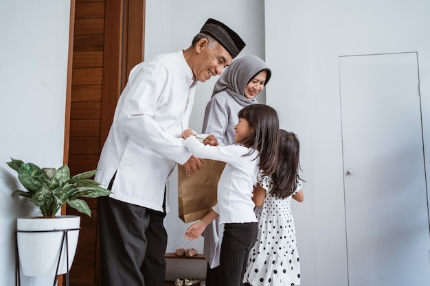 Happy asian family giving present to their muslim grandparents during eid mubarak celebration. suprise gift to family