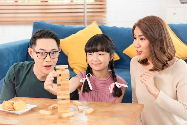 自宅のリビングルームでブロックゲームを楽しんでいる幸せなアジアの家族。