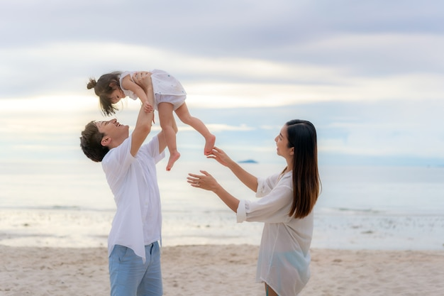 Happy asian family on holiday on the beach