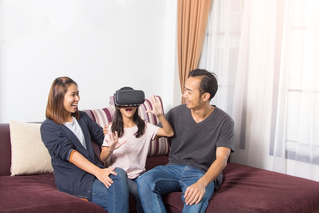 Happy asian family at home. girl playing with virtual reality goggles, vr headset