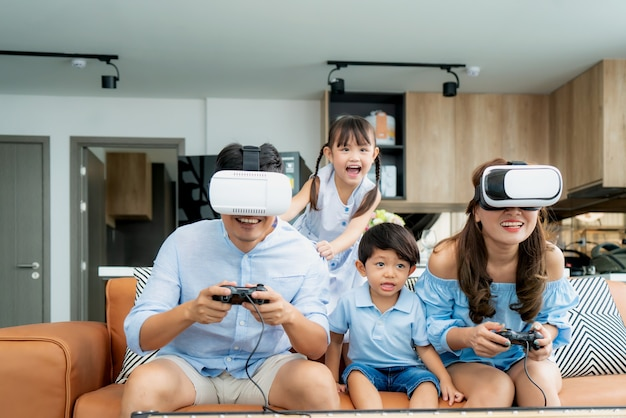 Happy asian family at home on living room sofa having fun playing games