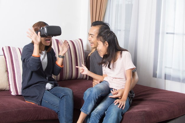 Happy asian family at home wearing virtual reality goggles