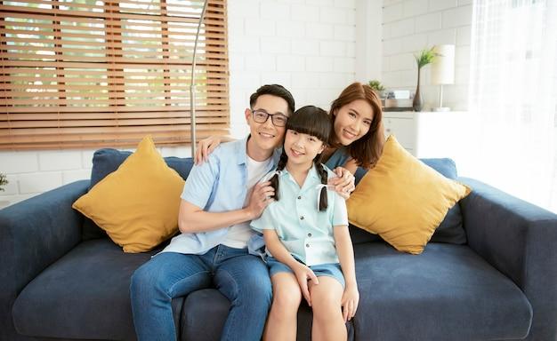 幸せなアジアの家族が自宅のリビングルームのソファで一緒に抱き締めます。