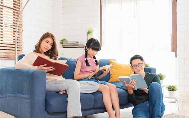 幸せなアジアの家族は、週末を家の屋内のソファで一緒に過ごし、リラックスして本を読んで楽しんでいます。