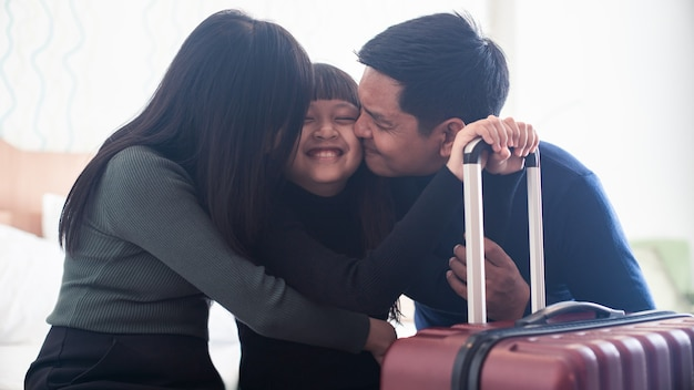 Happy asian family kissing daughter at room in hotel