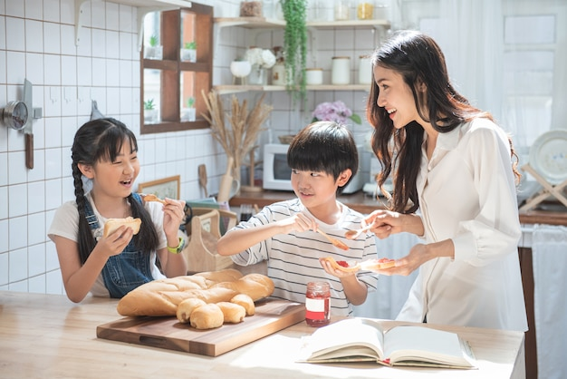 Happy asian family in the kitchen. mother and son and daughter and children spread strawberry yam on bread, leisure activities at home.