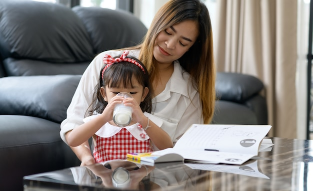 Happy asian family mom and daughter drink milk at home