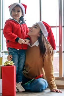 Happy asian family mom and daughter in red and white santa claus hat and sweater smiling playing together near christmas pine tree with glitter decorating items and present gift boxes in xmas evening.