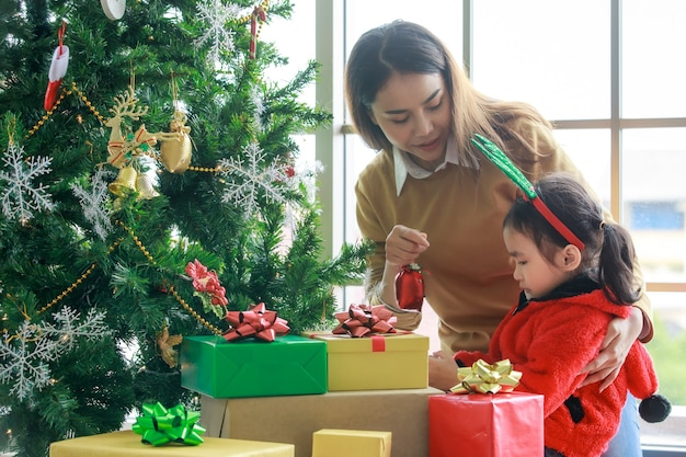 Happy asian family mom hug and teach daughter in red sweater and reindeer antler headband decorating christmas pine tree with glitter hanging items celebrating xmas eve event in living room at home.