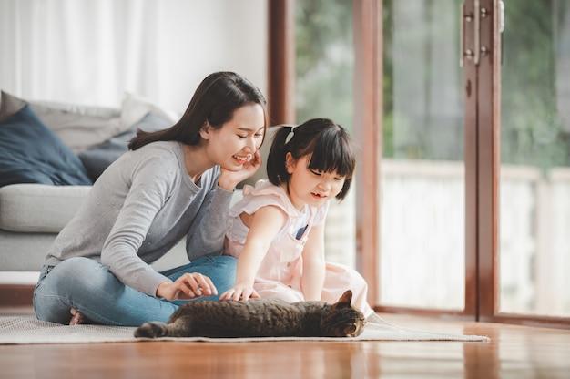 Счастливая азиатская семья мать и дочь, играя с кошкой дома в гостиной. сосредоточен на матери