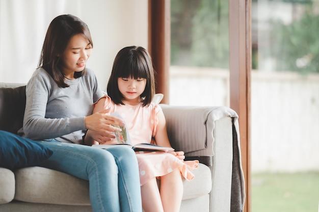 행복 한 아시아 가족 엄마와 딸 집에서 거실에서 책을 읽고 소파에 앉아
