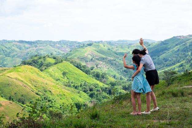Счастливая азиатская мать и дочь семьи стоя на верхней части красивой горы держа поднятые руки
