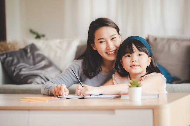 행복 한 아시아 가족 어머니와 딸이 집에서 함께 공부합니다. 딸에 초점을 맞춘 이미지