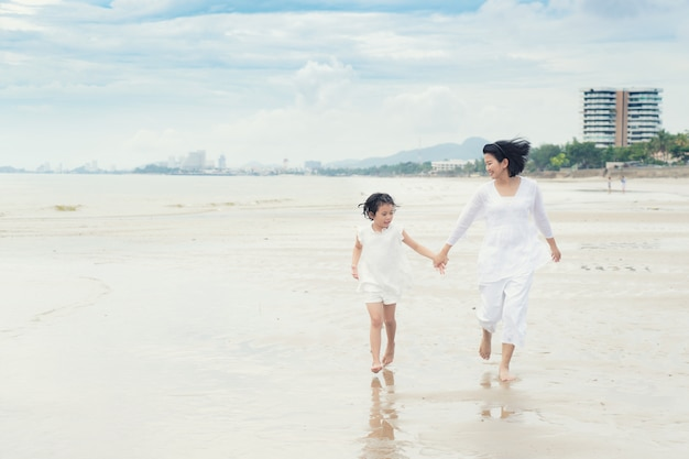 Happy asian family mother and child daughter run, laugh and play at beach.