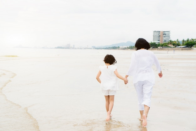 Happy asian family mother and child daughter run, laugh and play at beach