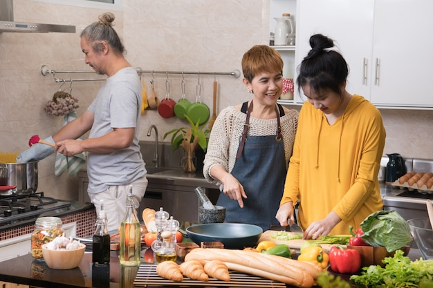 Happy asian family of mother father and daughter cooking in kitchen making healthy food together feeling fun