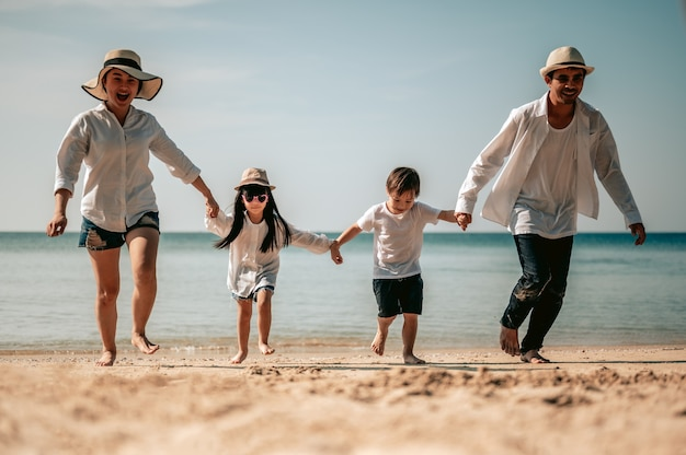Happy asian family parents are holding hands their children and walking on the beach in holiday