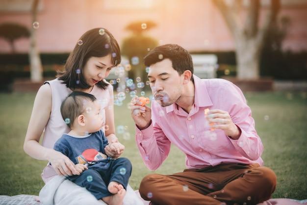ハッピーアジアの家族のピクニックと休暇中の公園でリラックス