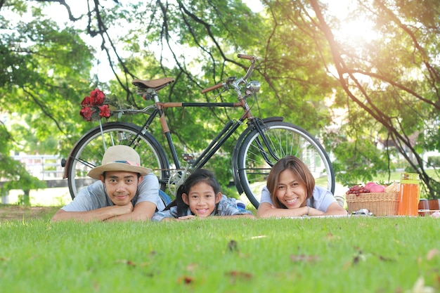 Happy asian family picnic lying in the garden togetherness relaxation concept