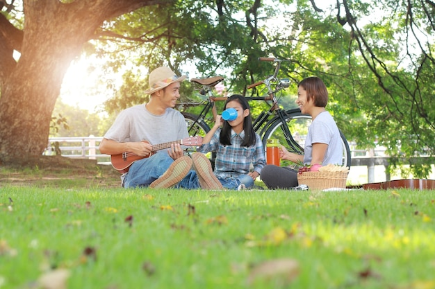 Happy asian family picnic in the park togetherness relaxation concept