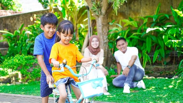 Счастливая азиатская семья, играя на велосипеде вместе в парке