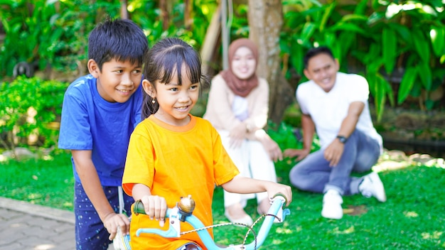 Happy asian family playing bike together in the park
