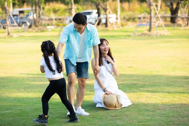 公園で子供たちと遊んで幸せなアジアの家族。幸せな家族の父母と子娘