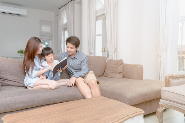 Happy asian family reading storybook at home