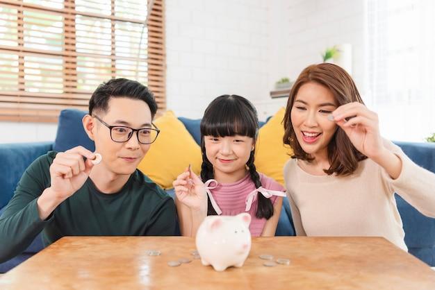 幸せなアジアの家族は、貯金箱の豚でお金を節約します。将来のコンセプトへの投資。