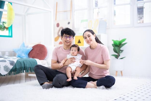 집에서 어린이 침실에 앉아 행복한 아시아 가족 프리미엄 사진