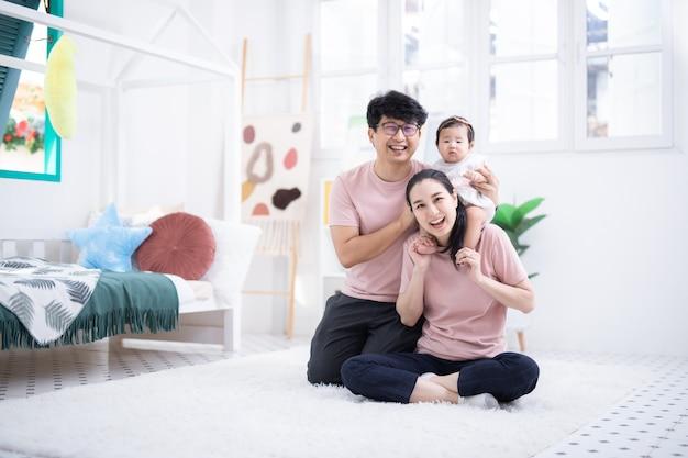 집에서 어린이 침실에 앉아 행복한 아시아 가족