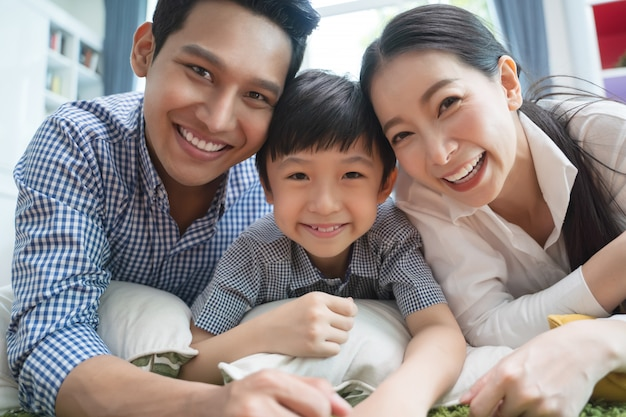 Happy asian family spending time together on sofa in living room.