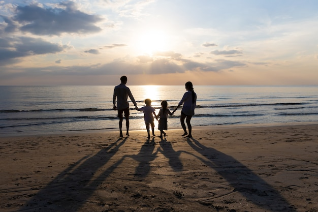 Happy asian family on summer vacation father, mother, son and daughter holding hands running down to the seashore together. sunset in sea. relax holiday and travel concept.