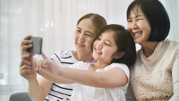 Happy asian family take selfie photo shot together by smartphone, multi generation of asia