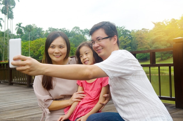 Happy asian family taking a outdoor selfie in a city park.