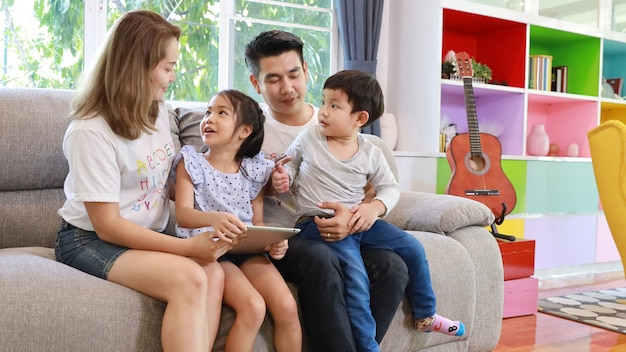 Happy asian family teaching children son and daughter how to use tablet
