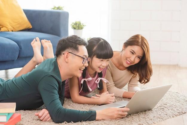 Счастливая азиатская семья, используя ноутбук вместе на диване у себя дома в гостиной.