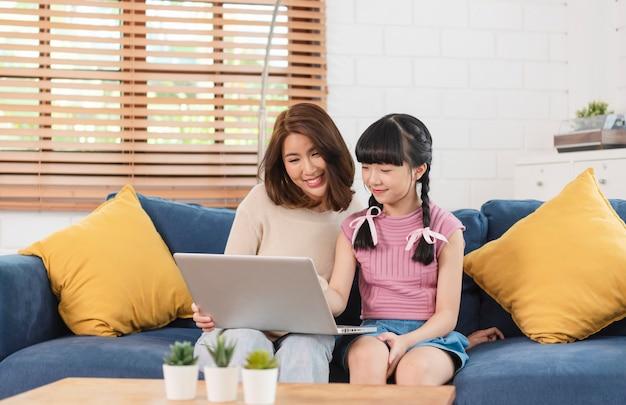 행복한 아시아 가족은 집 거실의 소파에서 컴퓨터 노트북을 함께 사용합니다.