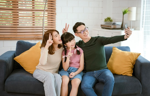 Happy asian family using smartphone taking a selfie photo together on sofa at home living room.