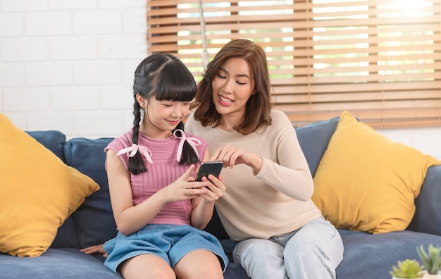 Happy asian family using smartphone together on sofa at home living room.