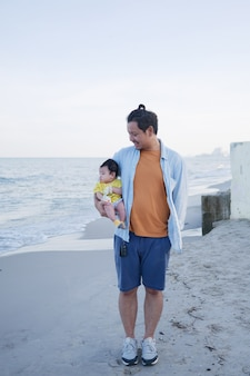 Happy asian family vacation, a father holds his cute little baby at the beach in summer, he looking at his baby, family sea trip