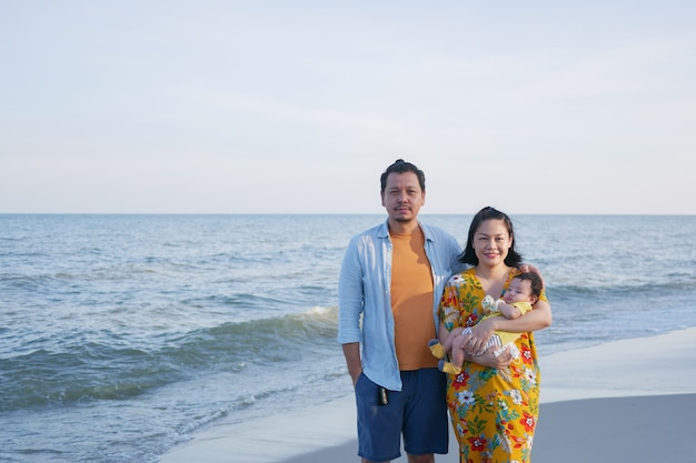 幸せなアジアの家族の休暇、ママとパパは夏のビーチでかわいい赤ちゃんを抱き、カメラを見て、家族の海の旅