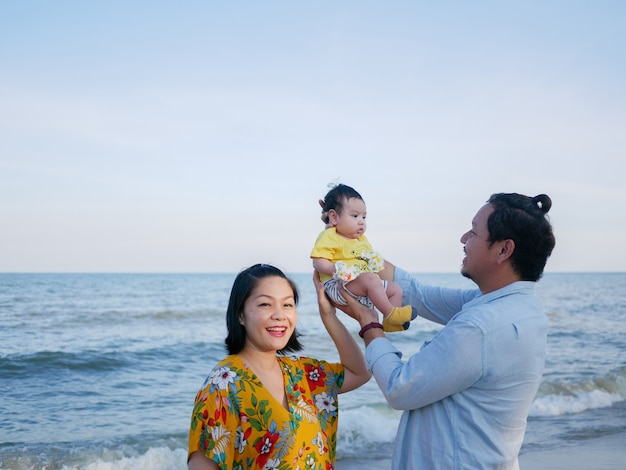 Happy asian family vacation, mom and dad hold a cute baby at the beach in summer, family sea trip