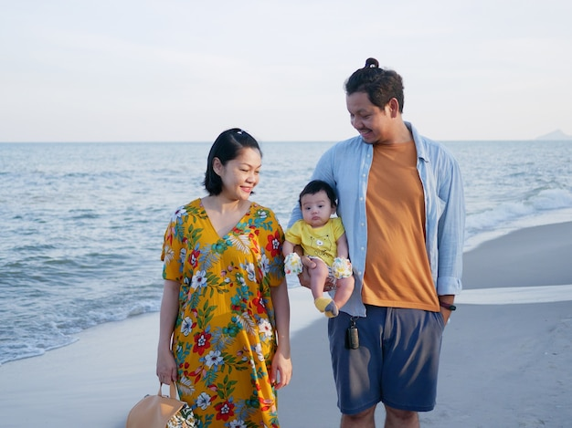 Happy asian family vacation, mom and dad hold a cute baby on the beach, they look at the baby