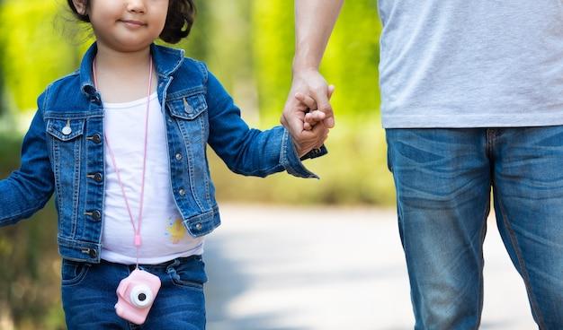 公園で子供たちと一緒に歩いて手をつないで幸せなアジアの家族。幸せな家族の父母と子娘