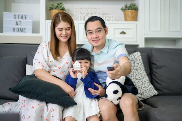 A happy asian family watching tv is spending time together at home on weekends