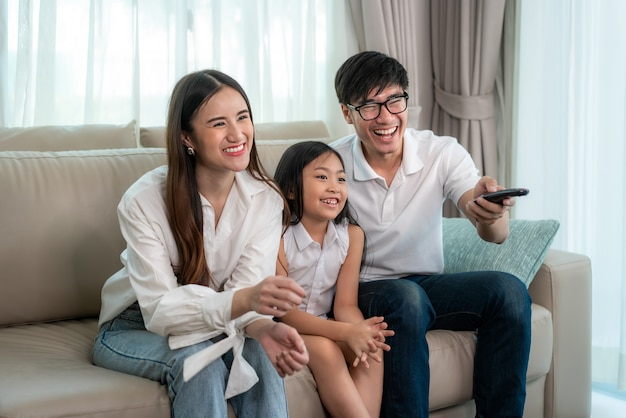 Happy asian family watching tv on the sofa