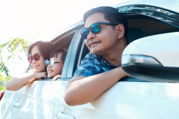 Happy asian family wearing sunglasses and sitting in the car looking out windows