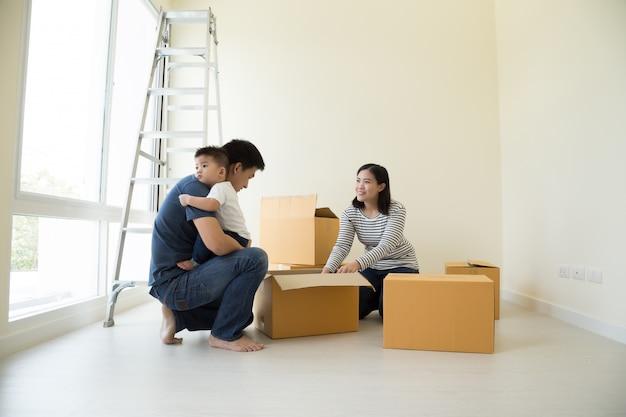 Счастливая азиатская семья с картонными коробками в новом доме в день переезда