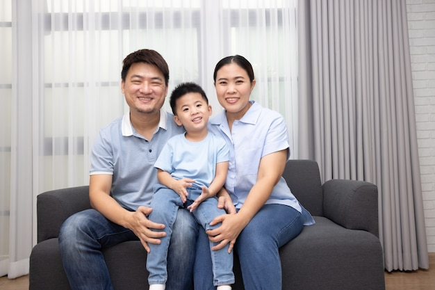 Happy asian family with little son sitting on sofa together at home